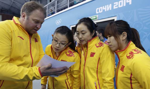 Team China coach Marcel Rocque, of Canada, talks with his players, from left, Wang Bingyu, Yue Qingshuang, and Jiang Yilun, after the first day of curling training at the 2014 Winter Olympics, Saturday, Feb. 8, 2014, in Sochi, Russia. (AP Photo/Robert F. Bukaty)