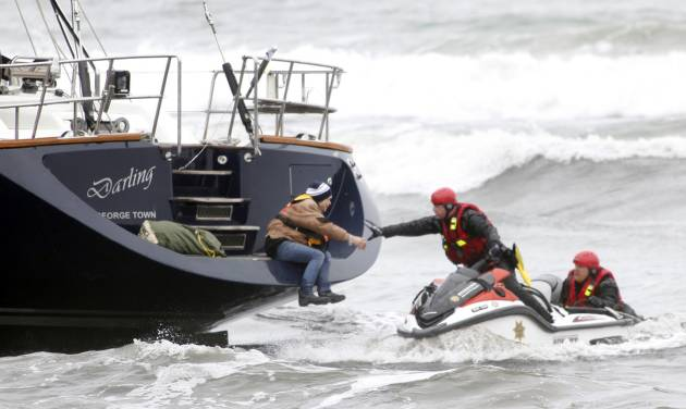Rescuers attempt to grab a woman off the back of the 82-foot-long sailboat, the Darling, stuck in the surf off Pacifica, Calif., Monday March 4, 2013. Three people were arrested Monday after they stocked a stolen yacht with pizza and beer, and then ran the vessel aground on a Northern California beach, authorities said. The boat was stolen from Sausalito, Calif. (AP Photo/Bay Area News Group, Karl Mondon)