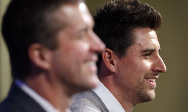 Baltimore Ravens tight end Dennis Pitta, right, sits alongside head coach John Harbaugh as he discusses his new five-year contract during an NFL football news conference, Wednesday, March 5, 2014, at the Ravens practice facility in Owings Mills, Md.  (AP Photo/Patrick Semansky)