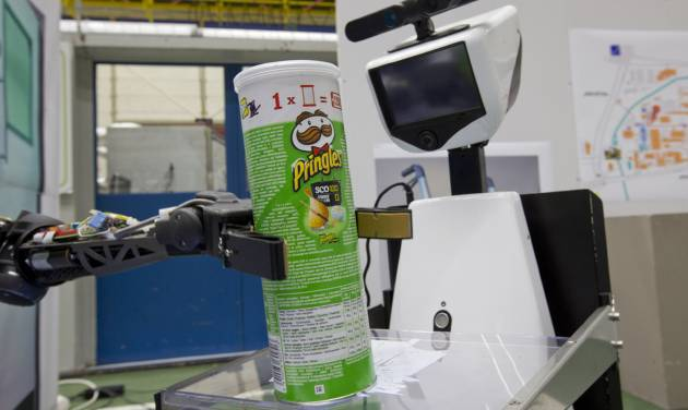 "A robotic arm, left, puts a package of Pringles on the serving tray of another robot to deliver it to an imaginary patient in a mock hospital room at the Technical University of Eindhoven, Netherlands, Wednesday Jan. 15, 2014. A group of five of Europe's top technical universities, together with technology conglomerate Royal Philips NV, are launching an open-source system dubbed ""RoboEarth"" Thursday. The heart of the mission is to accelerate the development of robots and robotic services via efficient communication with a network, or ""cloud"". (AP Photo/Peter Dejong)"