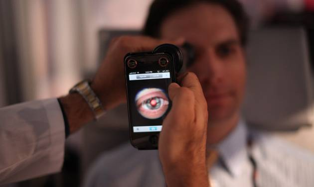 This image provided by TEDMED, shows a medical student preparing to photograph the inside of someone's eye using a special tool that taps a smartphone's camera during a recent TEDMED conference in Washington. Companies are developing a variety of miniature medical tools that hook onto smartphones to provide almost a complete physical. The hope is that this mobile medicine will help doctors care for patients in new ways, and also help people better monitor their own health. (AP Photo/TEDMED)