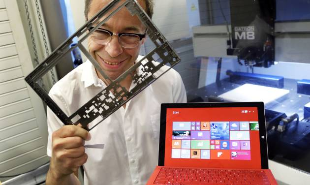 In this photo taken July 3, 2014, Ralf Groene, chief designer for the Microsoft Surface tablet computer, poses for a photo with a Surface 3 Pro tablet, right, in front of a milling machine used to produce parts for the computer, like the one he is holding at left, in Redmond, Wash. As Microsoft competes with Apple and other companies for hardware sales, the software giant has put a new emphasis on design. (AP Photo/Ted S. Warren)