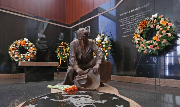 Flowers are displayed at the memorial to the 10 men killed in the Jan. 27, 2001 Oklahoma State plane crash before the start of an NCAA college basketball game between West Virginia and Oklahoma State in Stillwater, Okla., Saturday, Jan. 25, 2014. (AP Photo/Sue Ogrocki)