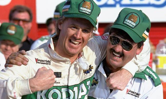 FILE - In this Oct. 10, 1988, file photo ,NASCAR driver Rusty Wallace of St. Louis, Mo., left, hugs his crew chief Barry Dodson in victory lane after winning the Oakwood Homes 500 auto race at the Charlotte Motor Speedway in Concord, N.C. Wallace, a winner of 55 races and the 1989 championship, will be inducted Friday night, Feb. 8, 2013, into the NASCAR Hall of Fame, along with Buck Baker and Herb Thomas; car owner Cotton Owens and crew chief, mechanic and engine builder Leonard Wood. (AP Photo/Robert Willett, File)