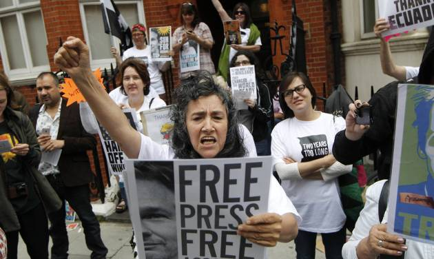 Supporters of WikiLeaks founder Julian Assange hold a vigil outside the Ecuadorian Embassy in London to mark his two years in refuge at the embassy, Thursday, June 19, 2014. Julian Assange entered the embassy in June 2012 to gain political asylum to prevent him from being extradited to Sweden, where he faces allegations of sex crimes, which he denies.(AP Photo/Sang Tan)