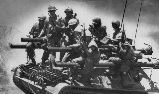 """FILE -In this July 3, 1968 file photo, Marines of the first battalion, ninth marines ride on a lightweight tank-like vehicle carrying four 106mm recoilless rifles near Khe Sanh in Vietnam. The Marine Corps is holding a deactivation ceremony on Friday, Aug. 29, 2014, for the 1st Battalion, 9th Marine Regiment, 2nd Marine Division, a battalion nicknamed the """"Walking Dead."""" (AP Photo/Stone)"""
