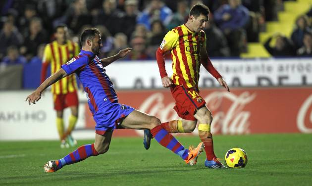 Barcelona's Lionel Messi from Argentina duels for the ball with Levante's Vyntra from the Czech Republic during their La Liga soccer match at the Ciutat de Valencia stadium in Valencia, Spain, Sunday, Jan. 19, 2014. (AP Photo/Alberto Saiz)