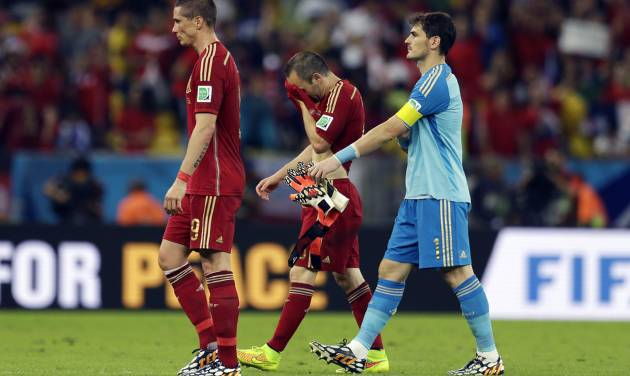From left, Spain's Fernando Torres, Andres Iniesta and goalkeeper Iker Casillas walk off the pitch following their group B World Cup soccer match between Spain and Chile at the Maracana Stadium in Rio de Janeiro, Brazil, Wednesday, June 18, 2014. Defending champion Spain was eliminated from the World Cup after losing to Chile 2-0.  (AP Photo/Natacha Pisarenko)