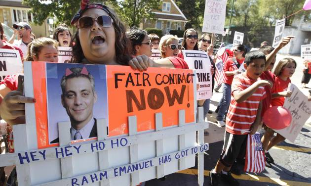 Striking Chicago Public School teacher Lanessa Mendoza pickets with fellow teachers from Peck Elementary School as Mayor Rahm Emanuel was visiting with students taking part at the Safe Haven program at Maranatha Church in Chicago, Monday, Sept. 10, 2012. The church is providing students with structured activities and a safe environment during the teachers' strike. Thousands of teachers walked off the job Monday in the nation's third-largest school district for the first time in 25 years after union leaders announced they were far from resolving a contract dispute with school district officials. (AP Photo/M. Spencer Green)