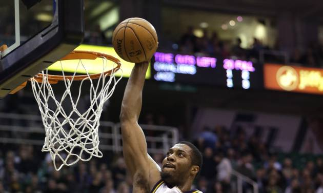 Utah Jazz's Derrick Favors (15) dunks the ball as Cleveland Cavaliers' Shaun Livingston (14) looks on in the fourth quarter during an NBA basketball game Saturday, Jan. 19, 2013, in Salt Lake City. The Jazz defeated the Cavaliers 109-98. (AP Photo/Rick Bowmer)