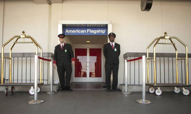 In this Thursday, March 14, 2013 photo, American Airlines skycaps Alex Abel Gonzalez, left, and Frederick Pearson await outside the AA Flagship lounge at Los Angeles International Airport, LAX. American's Flagship Check-in service, a VIP discreet and expedited check-in process offers personal access to agents for assistance with check-in and bag check, and a separate security line when flying through LAX and now Miami International Airport. (AP Photo/Damian Dovarganes)