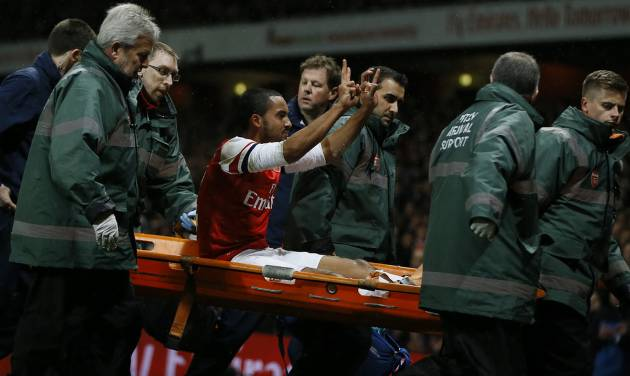 Arsenal's Theo Walcott, waves to the crowd as he is carried from the pitch on a stretcher after an injury during the English FA Cup third round soccer match between Arsenal and Tottenham Hotspur at the Emirates Stadium in London, Saturday, Jan. 4, 2014. (AP Photo/Kirsty Wigglesworth)