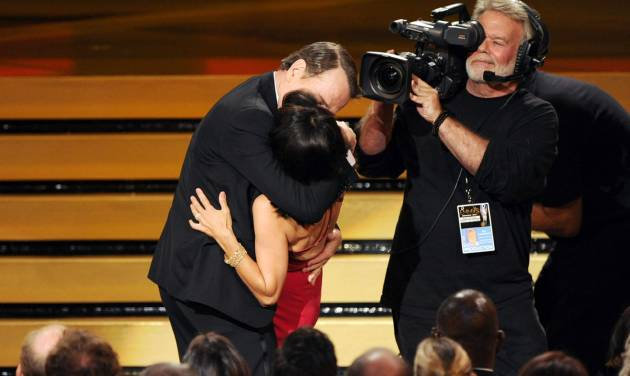 "Bryan Cranston kisses Julia Louis-Dreyfus, center front, as she accepts the award for outstanding lead actress in a comedy series for her work on ""Veep"" at the 66th Annual Primetime Emmy Awards at the Nokia Theatre L.A. Live on Monday, Aug. 25, 2014, in Los Angeles. (Photo by Chris Pizzello/Invision/AP)"
