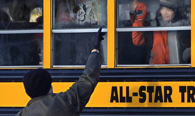 A man waves to a child on a bus on the first day of classes after the holiday break, in Newtown, Conn.,Wednesday, Jan. 2, 2013. Nearly three weeks after the shooting rampage at Sandy Hook Elementary School in Newtown, students and teachers from the school will return to class Thursday in the neighboring town of Monroe. (AP Photo/Jessica Hill)