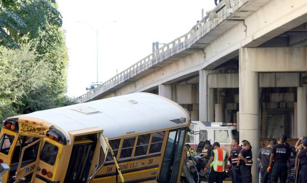 Emergency responders clean up after a collision caused a San Antonio ISD school bus to crash through a guardrail and fall off an elevated portion of Interstate 37 near Houston Street in downtown San Antonio, Texas. The school bus plunged about 15 feet from a Texas expressway overpass to the doorstep of a hotel below, miraculously causing only non-life-threatening injuries to the child and two adults aboard. (AP Photo/San Antonio Express-News, Helen L. Montoya)