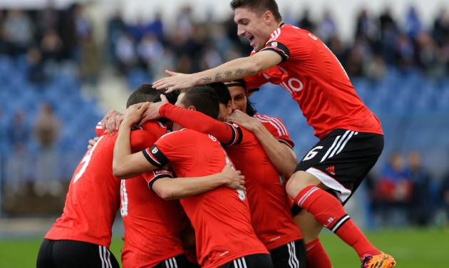 Benfica players celebrate after scoring the opening goal during their Portuguese league soccer match with Belenenses Sunday, March 2 2014, at Belenenses' Restelo stadium in Lisbon. Benfica defeated Belenenses 1-0 to remain at the top of the table. (AP Photo/Armando Franca)