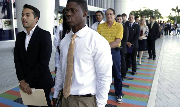 FILE - In this Wednesday, Oct. 23, 2013 file photo, Luis Mendez, 23, left, and Maurice Mike, 23, wait in line at a job fair held by the Miami Marlins, at Marlins Park in Miami. The labor Department issues the December jobs report, the last one for 2103, on January 10. 2014. (AP Photo/Lynne Sladky, FIle)