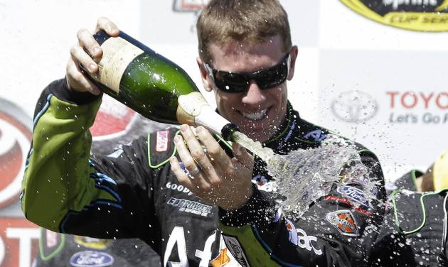 Carl Edwards sprays sparkling wine after winning the NASCAR Sprint Cup Series auto race Sunday, June 22, 2014, in Sonoma, Calif. Edwards won the race and Jeff Gordon finished second. (AP Photo/Eric Risberg)