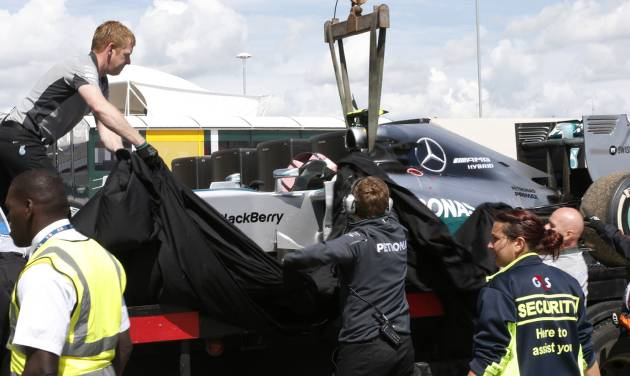 Mechanics cover the car of Germany's Nico Rosberg of Mercedes following  the British Formula One Grand Prix at Silverstone circuit, Silverstone, England, Sunday, July 6, 2014. Rosberg failed to complete the race due to mechanical failure. Britain's Lewis Hamilton of Mercedes won the race, Finland's Valtteri Bottas of Williams finished second and Australia's Daniel Ricciardo of Red Bull finished third.(AP Photo/Lefteris Pitarakis)