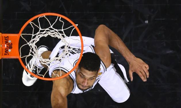 Miami Heat forward LeBron James, bottom, shoots as San Antonio Spurs forward Tim Duncan defends during Game 5 of the NBA basketball finals on Sunday, June 15, 2014, in San Antonio. (AP Photo/Andy Lyons, pool)