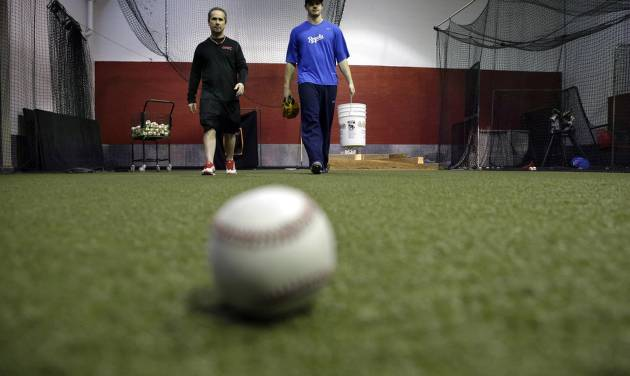 In this Feb. 24, 2014 photo, Kansas City Royals minor league pitcher John Walter, of Haddonfield, N.J., right, walks with Rob Potts, Program Director of  Power Train Sports Institute's AFC Baseball & Softball Academy in Cherry Hill, N.J. Potts is a 55-year-old former postal worker who spends his summers throwing batting practice to Chase Utley, Jimmy Rollins and Ryan Howard. When he's not at the ballpark, he's director of baseball operations at the baseball facility where several major and minor leaguers not only stay in shape during the winter, but hold pitching clinics for kids.  (AP Photo/Mel Evans)
