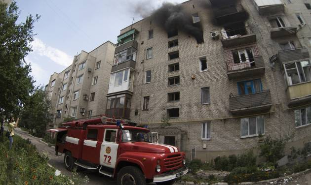 A fire truck arrives at a burning building after shelling in Maryinka village, outside the city of Donetsk, eastern Ukraine, Saturday, July 12, 2014. (AP Photo/Dmitry Lovetsky)