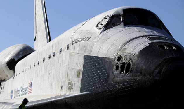 A workman helps in the process of prepping the space shuttle Endeavour to move the final few yards into a temporary hangar at the California Science Center in Los Angeles on Sunday, Oct. 14, 2012. After a 12-mile (19-kilometer) weave past trees and utility poles that included thousands of adoring onlookers, flashing cameras and even the filming of a TV commercial, Endeavour arrived at the California Science Center Sunday to a greeting party of city leaders and other dignitaries that had expected it many hours earlier. (AP Photo/Los Angeles Times, Luis Sinco, Pool)