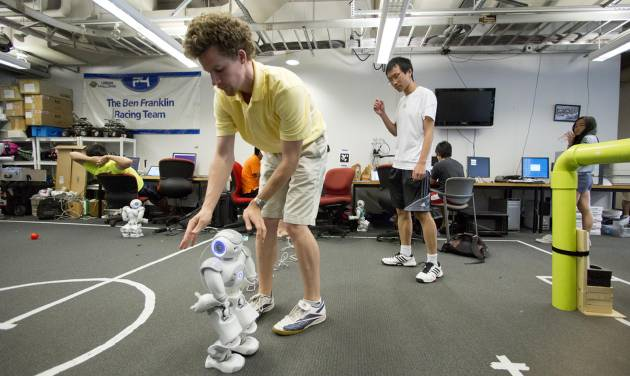 In this July 7, 2014, photo, Ph.D. candidate Stephen McGill works with a Nao RoboCup entree at the University of Pennsylvania in Philadelphia. The international robot soccer tournament called RoboCup takes place in Brazil right after the World Cup. The ultimate goal of the yearly event is bold: To create a robot team that can defeat the human World Cup winners by 2050.  (AP Photo/Matt Rourke)
