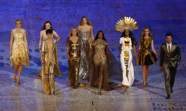"""FILE - This Sunday Aug. 12, 2012 file photo shows models, from left, Lily Cole, Karen Elson, Stella Tennant, Kate Moss, Lily Donaldson, Naomi Campbell, Jourdan Dunn and Georgia May Jagger walking with a male model during the Closing Ceremony at the 2012 Summer Olympics in London. Models had their moment at the closing ceremony of the London Olympics, with the likes of Kate Moss and Naomi Campbell bringing gold ballgowns, high heels and glamour to the stadium that had been home to sneakers and sweat. The unusual moment seemed to stump even the NBC announcers, who identified Campbell and Moss and otherwise stayed silent for much of the tribute set to David Bowie's """"Fashion."""" (AP Photo/Alastair Grant)"""