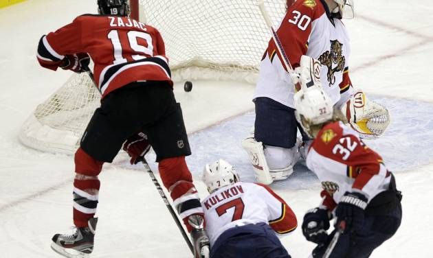 New Jersey Devils' Travis Zajac (19) scores the game-winning goal on Florida Panthers goalie Scott Clemmensen (30) as Dmitry Kulikov (7), of Russia, and Kris Versteeg (32) defend during the overtime of Game 6 of a first-round NHL hockey Stanley Cup playoff series, Tuesday, April 24, 2012, in Newark, N.J. The Devils won 3-2, forcing Game 7. (AP Photo/Julio Cortez)