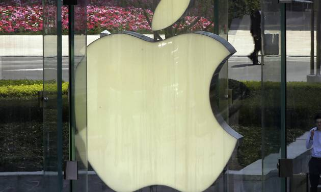 FILE - In this April 2, 2013, file photo, a man smokes near the logo of Apple in Shanghai. Apple is expected to unveil its latest version of the iPhone on Tuesday, Sept. 10, 2013. (AP Photo/Eugene Hoshiko, File)