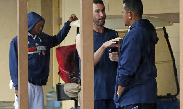 Detroit Tigers' Justin Verlander, center, talks with Miguel Cabrera, right, as Tigers players gather outside their locker room while waiting for an exhibition spring training baseball game between the Detroit Tigers and the Philadelphia Phillies to be called due to rain in Lakeland, Fla., Thursday, March 6, 2014. (AP Photo/Gene J. Puskar)