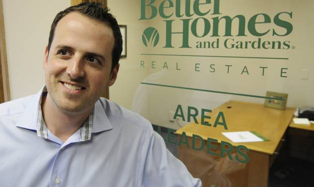 "In this Tuesday, Oct. 9, 2012 photo, Andy Asbury, owner of ""Better Homes & Gardens Real Estate Area Lenders"", is shown at his office in Edina, Minn. Asbury, who has the business to support more agents, hired a full-time employee just last Friday. Asbury said his sales are up 25 percent from a year ago and he's expecting them to rise further next year. (AP Photo/Jim Mone)"