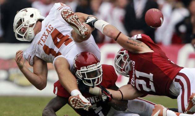 Texas quarterback David Ash (14) fumbles after he was sacked by Oklahoma linebacker Tom Wort (21) and defensive back Tony Jefferson (1) during the second half of an NCAA college football game at the Cotton Bowl Saturday, Oct. 13, 2012, in Dallas. Oklahoma won 63-21. (AP Photo/Michael Mulvey)