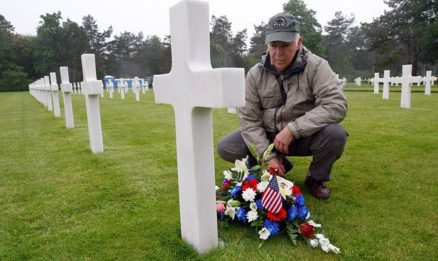 Paul Clifford, 70,  from Boston MA, USA, places flowers on the grave of Walter J. Gunther Jr, the uncle of his best friend, in the Normandy American Cemetery and Memorial, in Colleville sur Mer, France, Wednesday June 4, 2014.  World leaders and veterans prepare to mark the 70th anniversary of the D-Day invasion this week in Normandy. (AP Photo/Claude Paris)
