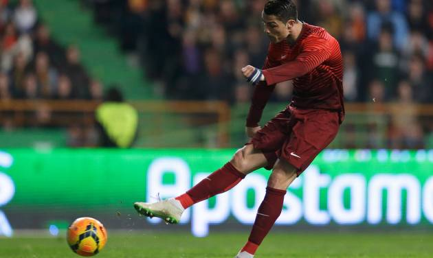 Portugal's Cristiano Ronaldo shoots to score the opening goal during their friendly soccer match with Cameroon Wednesday, March 5 2014, in Leiria, Portugal.  The game is part of both teams' preparation for the World Cup in Brazil. (AP Photo/Armando Franca)