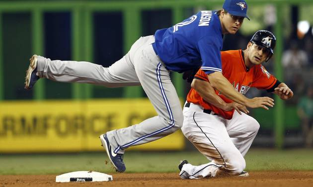After Miami Marlins runner Justin Ruggiano, right, was forced out at second both he and Toronto Blue Jays second baseman Kelly Johnson, front, watch to see if Omar Infante was safe at first during the fourth inning of a baseball game in Miami, Saturday, June 23, 2012. Infante was safe at first. (AP Photo/J Pat Carter)