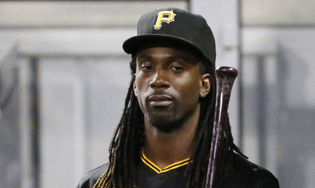 Pittsburgh Pirates' Andrew McCutchen tosses a bat as he walks through the dugout during the eighth inning of a baseball game against the San Diego Padres in Pittsburgh, Friday, Aug. 8, 2014. McCutchen is recovering from a rib injury and did not play. The Pirates won 2-1. (AP Photo/Gene J. Puskar)