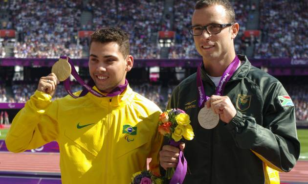 Gold medal winner Brazil's Alan Oliveira, left, poses for photographers beside silver medalist South Africa's Oscar Pistorius during after the medal ceremony for the men's 200m T44 category final during the athletics competition at the 2012 Paralympics, Monday, Sept. 3, 2012, in London. Pistorius, who won a legal battle to compete wearing carbon-fiber blades alongside able-bodied runners at the Olympics last month, suggested after the race that Oliveira ran with longer prosthesis than should be allowed. (AP Photo/Raissa Ioussouf)
