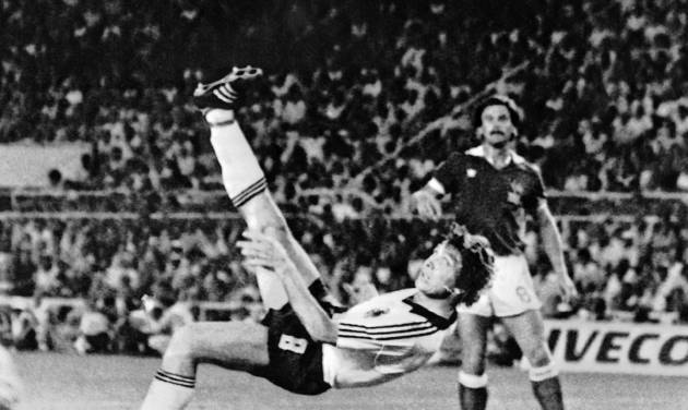FILE - In this July 8, 1982 file photo, West Germany's Klaus Fischer scores the third goal and equalizes, in the World Cup semi-final soccer match against France, in Seville, Spain. On this day: West Germany defeats France in a penalty shoot out after a 3-3 draw. The game was marred by a terrible injury to France's Patrick Battiston following a collision with German goalkeeper Harald Schumacher.  (AP Photo/File)