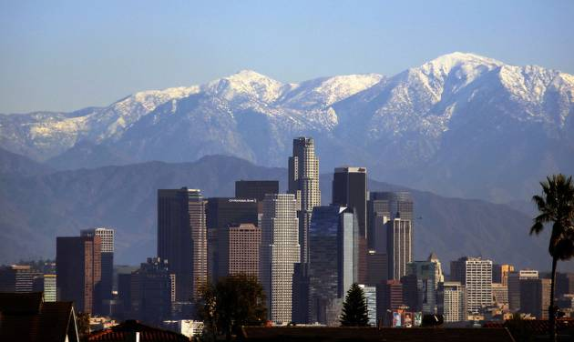Snow-covered San Gabriel mountains rise behind downtown Los Angeles Wednesday, Dec. 19, 2012. Winds that tore down trees and power lines eased Wednesday in Southern California but chilly weather remained and the cold was expected to deepen, with sub-freezing temperatures possible. (AP Photo/Nick Ut)