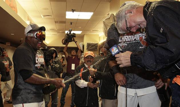 San Francisco Giants' Pablo Sandoval, left, sprays Champagne during a television interview after the Giants defeated the San Diego Padres to win the National League West Division title after a baseball game, Saturday, Sept 22, 2012, in San Francisco. The Giants won 8-4. (AP Photo/Ben Margot, Pool)