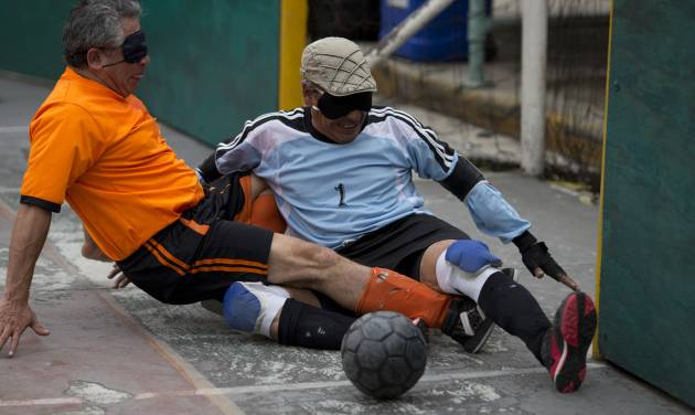"""In this Sunday, June 8, 2014 photo, Italia's goalkeeper Miguel Angel Canela stops a scoring attempt by Marco Antonio Camarillo of Leones Negros, during the league final in Mexico City. Following the match, Canela was recognized with the 2014 trophy for best goalie. Camarillo, 53, was pleased with his performance as well, after scoring one goal in the final. His wife came out to watch him play. """"She is afraid of me being hit, or falling, but she shares my love of football,"""" says Camarillo. (AP Photo/Rebecca Blackwell)"""