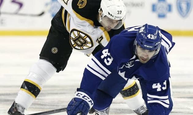 Toronto Maple Leafs' Nazem Kadri (43) reaches for the puck past Boston Bruins' Patrice Bergeron during the first period of an NHL hockey game in Boston on Monday, March 25, 2013. (AP Photo/Winslow Townson)