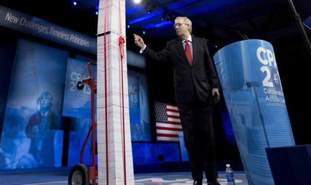 "FILE - In this March 15, 2013, file photo the Senate Minority Leader, Republican Mitch McConnell of Kentucky, points to a 7-foot stack of ""Obamacare"" regulations to underscore his disdain during the 40th annual Conservative Political Action Conference in National Harbor, Md.  McConnell said Democrats have been predicting for years that Americans would learn to love the health care overhaul and that has not happened. ""I agree that it will be a big issue in 2014,"" he said. ""I think it will be an albatross around the neck of every Democrat who voted for it. They are going to be running away from it, not toward it."" (AP Photo/Manuel Balce Ceneta, File)"