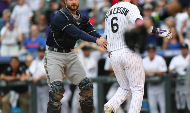 At home plate, Milwaukee Brewers catcher Jonathan Lucroy, left, tags out Colorado Rockies' Corey Dickerson who was trying to stretch a triple into an inside-the-park home run in the ninth inning of the Brewers' 6-5 victory in a baseball game in Denver, Sunday, June 22, 2014. (AP Photo/David Zalubowski)