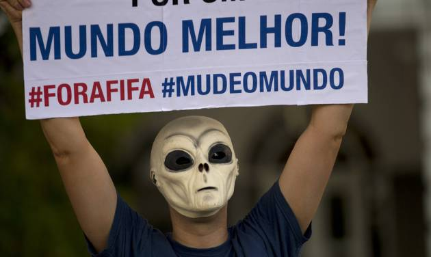 "A man wearing an ET mask holds a sign that reads in Portuguese ""For a better world! Get out FIFA, Change the World"" during a protest against the upcoming World Cup soccer tournament in Rio de Janeiro, Brazil, Saturday, Jan. 25, 2014. Last year, millions of people took to the streets across Brazil complaining of higher bus fares, poor public services and corruption while the country spends billions on the World Cup, which is scheduled to start in June. (AP Photo/Silvia Izquierdo)"