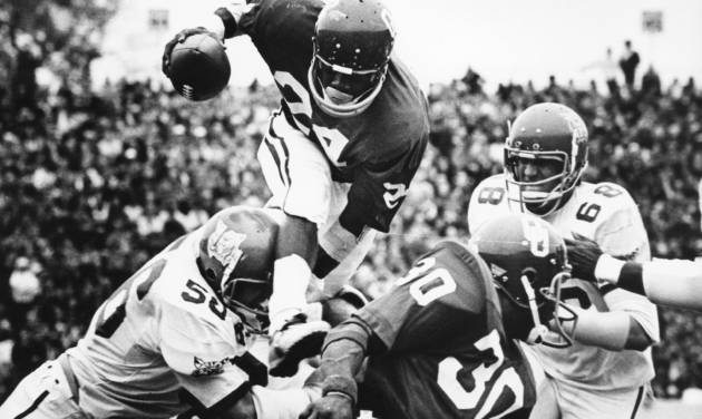 Sooner freshman Joe Washington leaps over a Kansas State player during a Oct. 28, 1972, game. Providing a block is teammate Greg Pruitt (30).  The Sooners beat the Wildcats 52-0. PHOTO BY JIM ARGO, THE OKLAHOMAN ARCHIVES