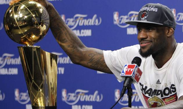 The Miami Heat's LeBron James rests his hand on the the Larry O'Brien NBA Championship Trophy during a news conference after Game 5 of the NBA finals basketball series against the Oklahoma City Thunder, Friday, June 22, 2012, in Miami. The Heat won 121-106 to become the 2012 NBA Champions.(AP Photo/Lynne Sladky)