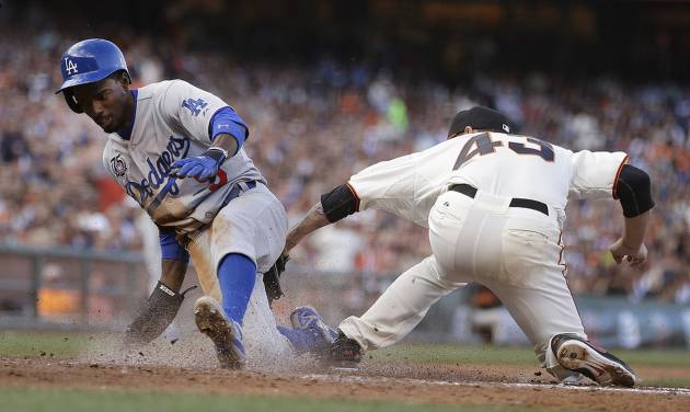 Los Angeles Dodgers' Dee Gordon, left, scores past San Francisco Giants pitcher Jake Peavy in the fifth inning of a baseball game Sunday, July 27, 2014, in San Francisco. (AP Photo/Ben Margot)